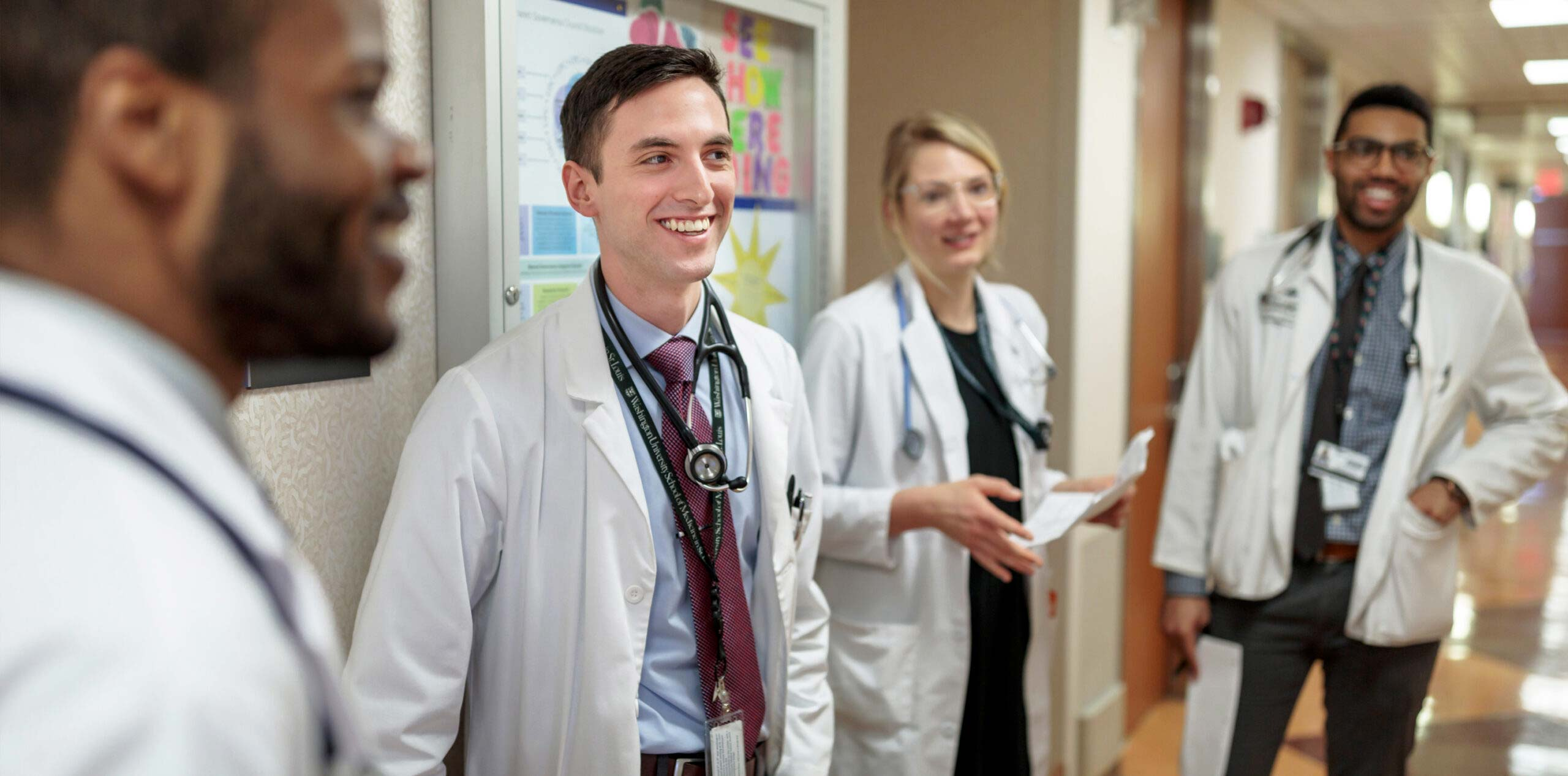 Four medical students in white coats smile as they confer in a hospital hallway